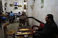 Egyptians watch a live television debate at a coffee shop in Cairo. Egypt held its first ever debate between presidential candidates on Thursday, as the two frontrunners for this month's election traded political accusations on television