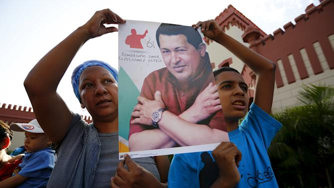 Supporters of late Venezuela's president Hugo Chavez sing the national anthem at his tomb during a ceremony to commemorate his 61st birthday at the 4F military fort in Caracas