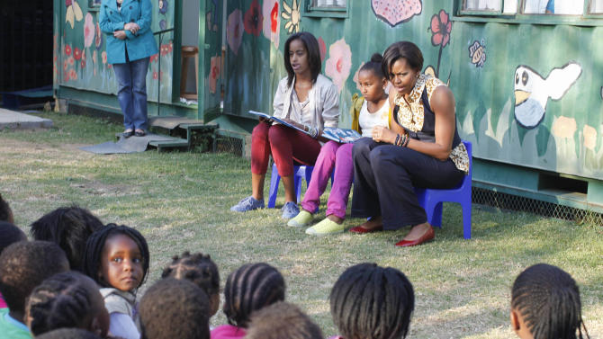 "FILE - In this June 21, 2011, file photo, first lady Michelle Obama, with daughters Malia, left, and Sasha, center, read from ""The Cat in the Hat,"" by Dr. Seuss, during their visit to the Emthonjeni Community Center in Zandspruit Township, Johannesburg, South Africa. Michelle Obama has a new look, both in person and online, and with the president's re-election, she has four more years as first lady, too. The first lady is trying to figure out what comes next for this self-described ""mom in chief"" who also is a champion of healthier eating, an advocate for military families, a fitness buff and the best-selling author of a book about her White House garden. For certain, she'll press ahead with her well-publicized efforts to reduce childhood obesity and rally the country around its service members. (AP Photo/Charles Dharapak, Pool, file)"