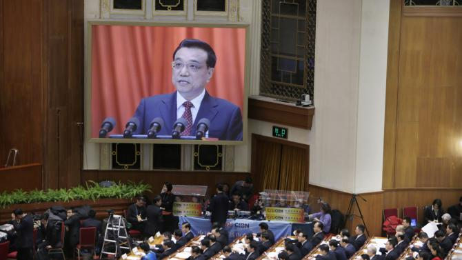 A screen shows Chinese Premier Li Keqiang delivering the government work report during the opening of the annual full session of the NPC in Beijing