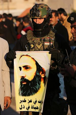 An Iraqi policeman holds a portrait of prominent Shiite…