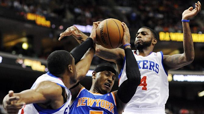New York Knicks' Carmelo Anthony (7) drives between Philadelphia 76ers' Thaddeus Young (21) and Dorell Wright (4) in the first half of an NBA basketball game, Monday, Nov. 5, 2012, in Philadelphia. (AP Photo/Michael Perez)
