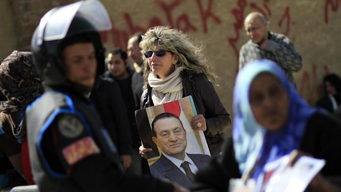 An Egyptian woman holds a photo of the ousted Egyptian President Mubarak outside a courtroom in Cairo, Egypt, Wednesday, Feb. 22, 2012. Egypt's ousted President Hosni Mubarak has turned down the chance to address the court on the last session before the verdict in his seven-month trial. (AP Photo/Khalil Hamra)
