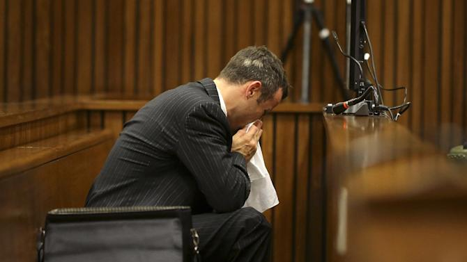 Oscar Pistorius blows his nose after reaching for a bucket as he listened to cross questioning about the events surrounding the shooting death of his girlfriend Reeva Steenkamp, in his second week in court during his trial in Pretoria, South Africa, Monday, March 10, 2014. Pistorius is charged with the shooting death of his girlfriend Steenkamp, on Valentines Day in 2013. (AP Photo/Siphiwe Sibeko, Pool)