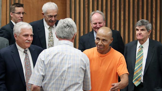 CORRECTS FIRST LAME TO LOUIS INSTEAD OF LEWIS - Louis Taylor shakes the hand of his first attorney from 1972, Howard Kashman, as his current defense team from Phoenix surrounds him after a hearing in Pima County Superior Court in Tucson, Ariz. on Tuesday April 2, 2013.  Taylor spent more than 40 years in prison for a 1970 hotel fire that killed 29 people agreed to a deal with prosecutors Tuesday that cleared the way for him to be released. The plea deal marks a stunning reversal for Taylor, who was 16 years old when he was arrested in the fire at the Pioneer Hotel in 1970, where employees of an aircraft company were celebrating at a Christmas party.  Prosecutors still believe that Taylor is guilty, but said they would not be able to pursue a new trial due to a lack of evidence and living witnesses.  (AP Photo/Arizona Daily Star, Benjie Sanders, Pool)