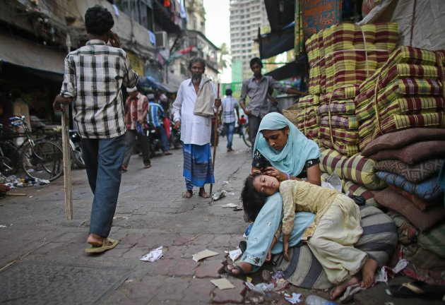 A woman cleans her daughter's hair as she sleeps in her lap by the roadside in Mumbai