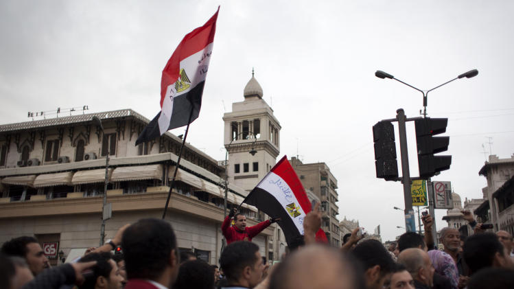 Egyptian protesters hold national flags and chant anti Muslim Brotherhood slogans during a rally in front of the presidential palace, in Cairo, Egypt, Tuesday, Dec. 4, 2012. Thousands of Egyptians massed in Cairo Tuesday for a march to the presidential palace to protest the assumption by the nation's Islamist president of nearly unrestricted powers and a draft constitution hurriedly adopted by his allies. (AP Photo/Nasser Nasser)