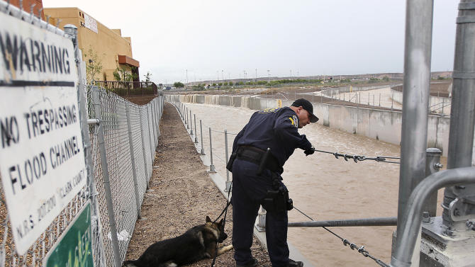 Henderson Police Officer James Mitchell and his dog Xaro conduct a search of the Duck Creek Channel for a missing teenager in Henderson, Nev., on Wednesday, Aug. 22, 2012. According to witnesses, the man was pulled into the heavily flooded wash as intense thunderstorms filled storm channels and sent water into roadways. (AP Photo/Las Vegas Review-Journal, Jason Bean) LOCAL TV OUT; LOCAL INTERNET OUT; LAS VEGAS SUN OUT