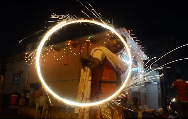 A minority Pakistani Hindu reveller waves sparklers on the occasion of Diwali in Karachi on November 13, 2012. Diwali, the festival of lights, is celebrated with jubilation and enhusiasm as one of the
