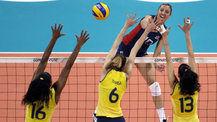 United States' Jordan Larson, top, spikes the ball over Brazil's Fernanda Rodrigues (16), Thaisa Menezes (6) and Sheilla Castro during a women's gold medal volleyball match at the 2012 Summer Olympics, Saturday, Aug. 11, 2012, in London. (AP Photo/Jeff Roberson)