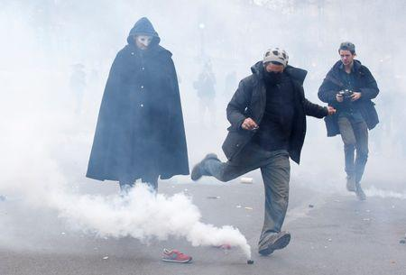 A demonstrator kicks a tear gas canister during clashes with CRS riot policenear the Place de la Republique after the cancellation of a planned climate march  ahead of the World Climate Change Conference 2015 in Paris