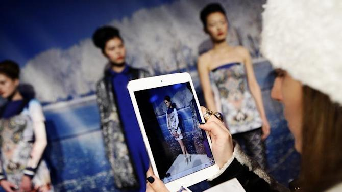 A woman takes a photo of models presenting creations from the Clover Canyon Autumn/Winter 2013 collection during New York Fashion Week