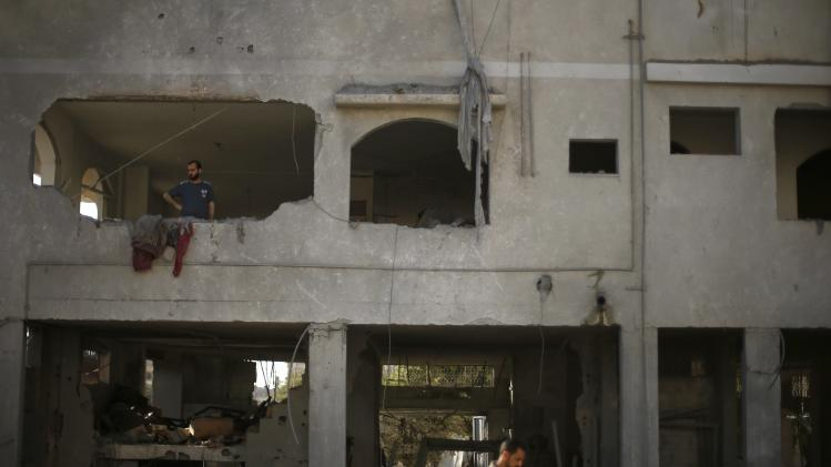A Palestinian looks out of his house that witnesses said was damaged during an Israeli airstrike in Gaza City