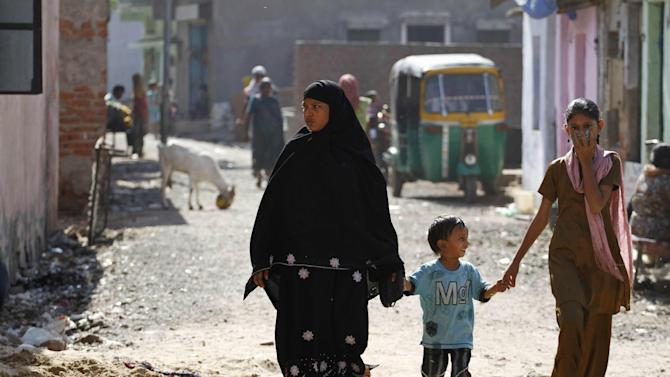 In this Thursday, Nov. 29, 2012 photo, an Indian Muslim woman along with children walks at one of the resettlement colonies of the survivors of 2002 riots in Ahmadabad, India. Eleven years after Modi became the chief minister of the western state of Gujarat - and 10 years after brutal anti-Muslim rioting left over a 1,100 people there dead - Modi is campaigning for his third term. Nearly everyone expects him to be swept into office, and the top leadership of his rightwing Bharatiya Janata Party is already hailing him as a future prime minister. But few politicians in India are as polarizing as Modi. (AP Photo/Ajit Solanki)