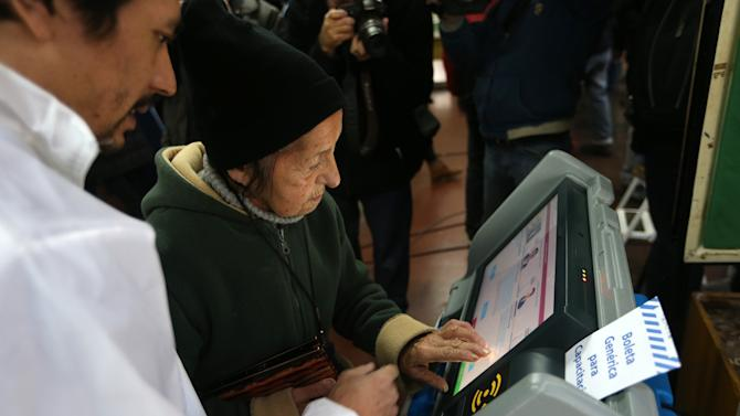 An elections officer shows an elderly woman how to use an electronic voting machine at a polling station, during mayoral elections in Buenos Aires, Argentina, Sunday, July 5, 2015. Voters go the polls to elect the new Buenos Aires' Mayor during an election in which the ruling party and the opposition measure forces with an eye on the next October general elections. (AP Photo/Daniel Jayo)
