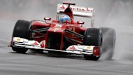 Ferrari Formula One driver Fernando Alonso of Spain rounds a curve in the rain (Reuters)