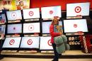 FILE - In this Nov. 28, 2014, file photo, a customer walks past a bank of flat screen televisions at a Target store in South Portland, Maine. Target said Wednesday, Nov. 18, 2015, its sales rose 1.9 percent at established locations in the third quarter, marking the fourth consecutive quarter the retailer has increased customer visits. (AP Photo/Robert F. Bukaty, File)