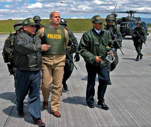 This file photo shows National Police officers escorting the leader of the rebel group FARC, known as Simon Trinidad (2-L), to a Colombian military airport in Bogota, in 2004. Colombia's leftist rebels said on Friday they are hoping the United States will allow Trinidad, held there, to participate in peace negotiations starting next month.