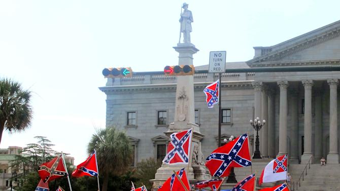 Supporters of keeping the Confederate battle flag flying at a Confederate monument at the South Carolina Statehouse wave flags during a rally in front of the statehouse in Columbia, S.C., on Saturday, June 27, 2015. Gov. Nikki Haley and a number of other state leaders have called for the removal of the flag following the shooting deaths of nine black parishioners in a church in Charleston.  (AP Photo/Bruce Smith)