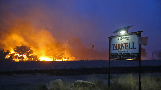 A wildfire burns homes in Yarnell, Ariz. on Sunday, June 30, 2013. An Arizona fire chief says the wildfire that killed 19 members of his crew near the town was moving fast and fueled by hot, dry conditions. The fire started with a lightning strike on Friday and spread to 2,000 acres on Sunday amid triple-digit temperatures. (AP Photo/The Arizona Republic, David Kadlubowski)