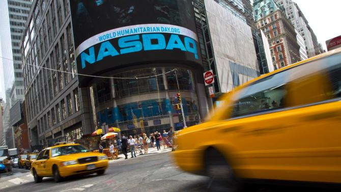 Taxi cabs drive past the Nasdaq MarketSite in New York's Times Square