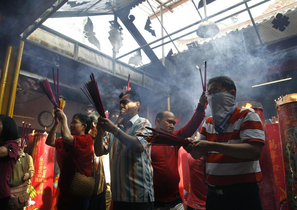 Indonesian ethnic Chinese burn incense sticks while praying during Lunar New Year celebrations at a temple in Jakarta, Indonesia,  Sunday, Feb. 10, 2013. (AP Photo/Achmad Ibrahim)