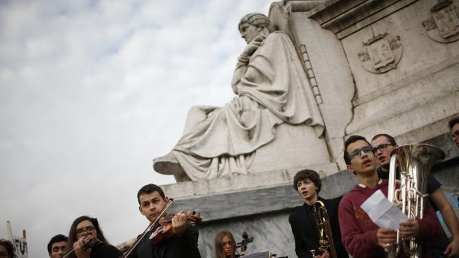 Students perform during a mock funeral march, organized by their peers from the National School of Music to protest against the condition of their school's building, in Lisbon
