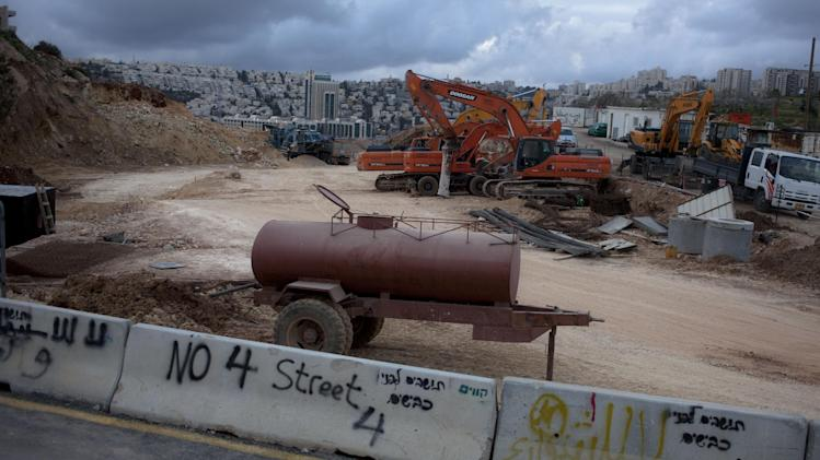 In this Thursday, Feb. 28, 2013 photo, the construction site of route 4 is seen in the Arab neighborhood of Beit Safafa in Jerusalem. A new Israeli highway project is threatening to upset Jerusalem's delicate ethnic balance by cutting through the heart of a quiet, upscale Arab neighborhood in order to link a large bloc of West Bank settlements to the city. (AP Photo/Sebastian Scheiner)