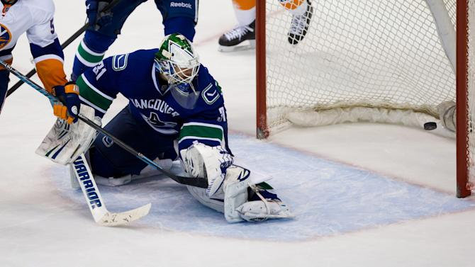 Vancouver Canucks' goalie Eddie Lack, of Sweden, allows a goal to New York Islanders' Matt Martin during third period NHL hockey action in Vancouver, British Columbia, on Monday March 10, 2014