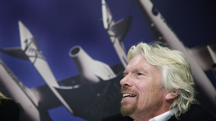 "Richard Branson, founder of the Branson Group,  talks during an interview in his company's office, Thursday, Dec. 1, 2011 in New York. Branson is promoting his book, ""Screw Business as Usual."" On the wall is a photograph of White Knight II, an aircraft built by Virgin Galactic.  (AP Photo/Mark Lennihan)"
