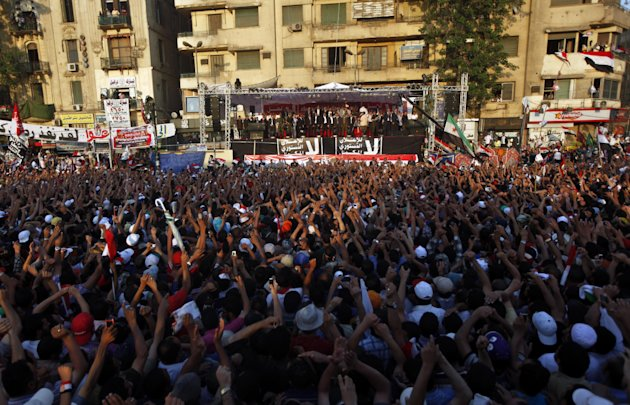 Egyptians wave to Egypt's President-elect, Mohammed Morsi, upon his arrival to give a speech at Tahrir Square in Cairo, Egypt, Friday, June 29, 2012. In front of tens of thousands of cheering supporters, Egypt's first Islamist and civilian president-elect vowed that nobody can take away his authority and symbolically read an oath of office on the eve of his official inauguration. (AP Photo/Khalil Hamra)