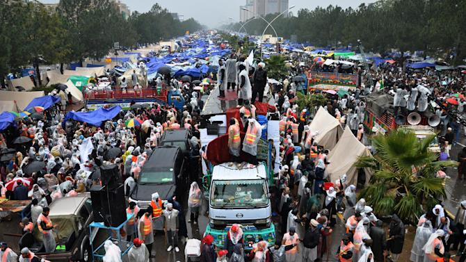 Supporters of Pakistani Sunni cleric Tahir-ul-Qadri, unseen, listen to their leader in Islamabad, Pakistan, Thursday, Jan. 17, 2013. Qadri is demanding the government be dissolved and replaced with a caretaker administration formed in consultation with the judiciary and the military. He also wants electoral reform to weed out corrupt politicians and prevent them from winning elections in the future. (AP Photo/B.K. Bangash)