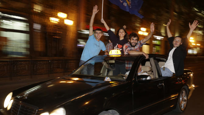 Opposition supporters reacts on the street in Tbilisi Georgia, Monday, Oct.1, 2012. Georgia's opposition coalition 'Georgian Dream' is leading the country's just-concluded parliamentary elections, according to the exit polls of a U.S.-based exit poll specialist company Edison Research and a Germany-based market research company GfK on Monday. Voters in Georgia are choosing a new parliament in a heated election Monday that will decide the future of President Mikhail Saakashvili's government. (AP Photo / Efrem Lukatsky)