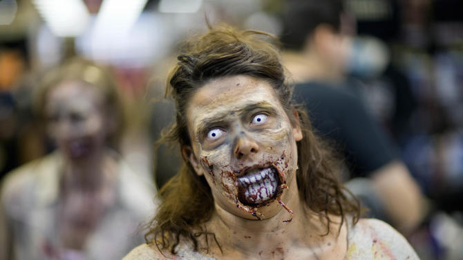 "Kim Kinney, of Atlanta, dressed as a zombie, walks through the floor of Walker Stalker Con, a convention based off the cable TV show ""The Walking Dead,"" Sunday, Nov. 3, 2013, in Atlanta. The convention, which ran through the weekend, was expected to draw about 10,000 participants says co-creator Eric Nordhoff. ""The Walking Dead"" characters battle zombies known as ""walkers"" in the streets of downtown Atlanta and in forests, small towns and a prison south of the city. The convention featured appearances by some of the show's actors as well as games, toys, comic and other memorabilia for fans of zombie, horror and science fiction. (AP Photo/David Goldman)"