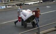 Youths push boxes of food as they cross a bridge in Cairo March 11, 2013. REUTERS/Amr Abdallah Dalsh