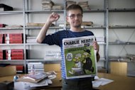 French satirical weekly Charlie Hebdo&#39;s publisher, known only as Charb, clenches his fist as he presents Wednesday&#39;s issue of the magazine to journalists in Paris. The magazine contains nude cartoons of the Prophet Mohammed