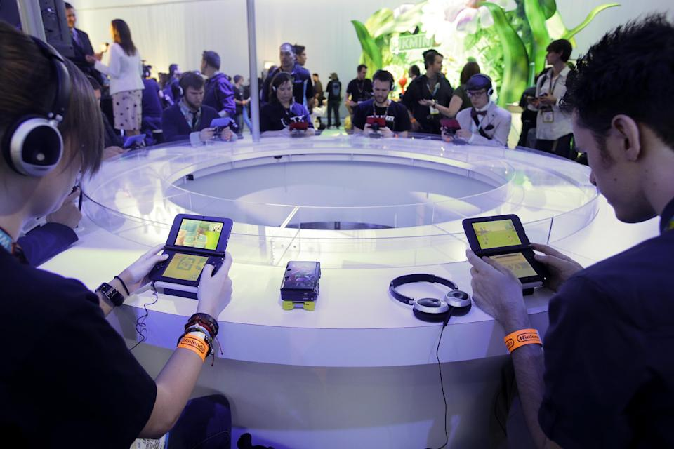 Attendees play video games on the Nintendo 3DS at the Nintendo Wii U software showcase during the E3 game show in Los Angeles, Tuesday, June 11, 2013. (AP Photo/Jae C. Hong)