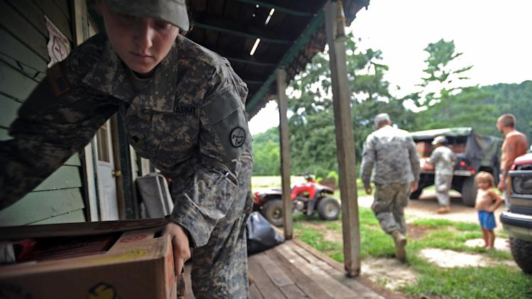 Spc. Megan Pena, left, with the W.Va. National Guard delivers a box of food to a home Thursday, July 5, 2012 in Heaters, W.Va. While utility crews continued working to restore power, members of the West Virginia National Guard went door to door with firefighters, police, church groups and others to reach people who were still awaiting help. Residents in the Heaters area have been without power since Friday, June 29, 2012 following a severe storm.  (AP Photo/Jeff Gentner)