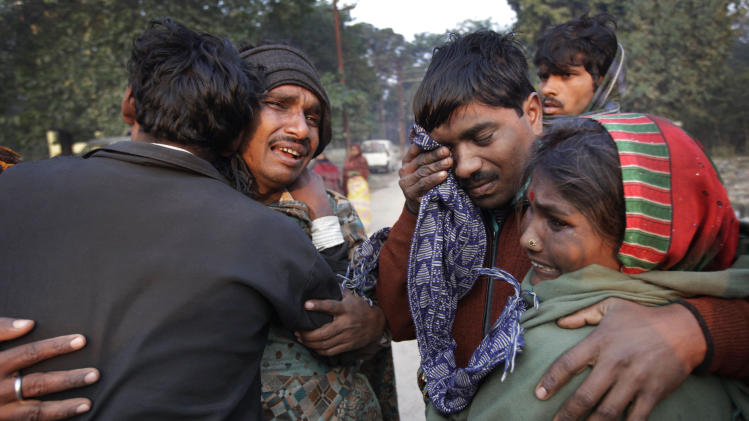 An Indian family whose relative died in a stampede at a railway station cry and comfort each other as they arrive to take the bodies from morgue, in Allahabad, India, Monday, Feb. 11, 2013. The death toll from the stampede in a train station rose to 36 on Monday in a northern India city where millions of devotees had gathered for a Hindu festival that is one of the world's largest religious gatherings. (AP Photo/Rajesh Kumar Singh)