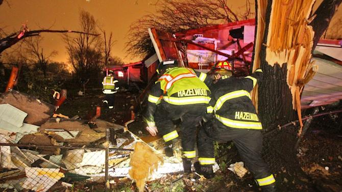 "Hazelwood fire fighters climb over a fence into the backyard of a home Lynn Haven Lane in Hazelwood that was damaged a storm on Wednesday, April 10, 2013.  Butch Dye, a hydrometeorological technician with the National Weather Service in St. Louis, Mo., said severe weather struck the suburb of Hazelwood.  ""We won't be able to confirm whether it was a tornado until teams get out there tomorrow,"" Dye said. (AP Photo/David Carson, Post-Dispatch)"