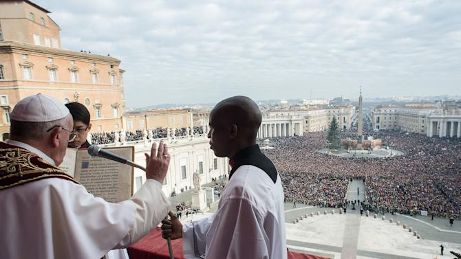 "Pope Francis blesses as he delivers a ""Urbi et Orbi"" (to the city and world) message from the balcony overlooking St. Peter's Square at the Vatican"