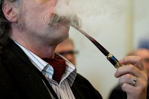"A delegate uses an e-pipe during ""The E-Cigarette Summit"" …"