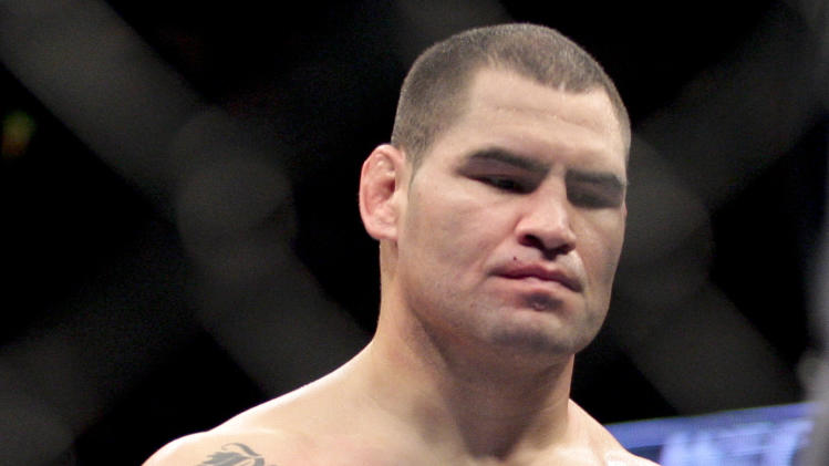 Cain Velasquez walks off after being defeated by Junior dos Santos, of Brazil, in their UFC mixed martial arts heavyweight title bout, Saturday, Nov. 12, 2011, in Anaheim, Calif. Dos Santos won by knockout in the first round. (AP Photo/Jason Redmond)