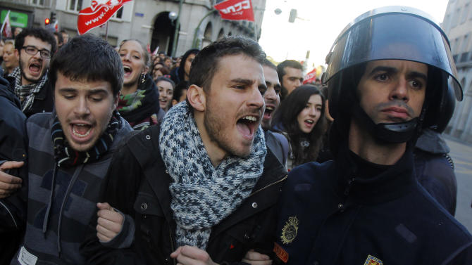 A protestor shout at  the police during a general strike in Madrid, Spain, Wednesday, Nov. 14, 2012. Spain's main trade unions stage a general strike, coinciding with similar work stoppages in Portugal and Greece, to protest government-imposed austerity measures and labor reforms. The strike is the second in Spain this year. (AP Photo/Andres Kudacki)