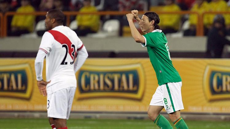 Bolivia's Pablo Escobar, right, celebrates after scoring Peru during a friendly soccer match in Lima, Peru, Friday Sept. 2, 2011. (AP Photo/Karel Navarro)