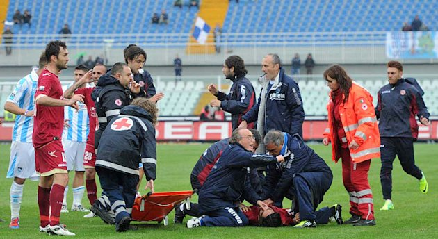 Medics assists Livorno's Piermario Morosini laying on the turf of the Pescara's Adriatico stadium, central Italy, Saturday, April 14, 2012, after he collapsed during a Serie B soccer match between Pes