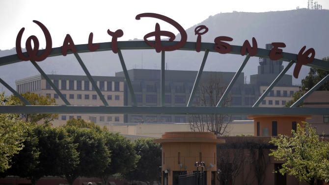 """FILE - In this Feb. 8, 2011 file photo, people stand near the entrance to the Walt Disney Studios in Burbank , Calif.  The Walt Disney Co.'s profit for the third-quarter beat analyst estimates but revenue came up short due to unchanged revenue at its movie studio despite a surge in profit from """"The Avengers."""" ( AP Photo/Jae C. Hong)"""