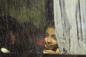 A girl looks out of a window as she sits in a bus which…