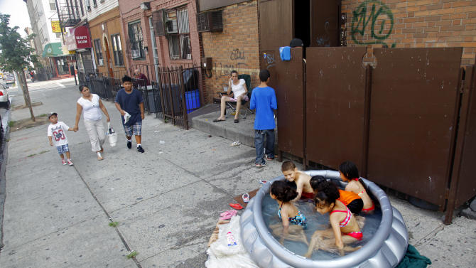 Stephanie Gracia, center, sit nearby and watch as her children and their friends cool off in an inflatable pool outside their apartment on Thursday, July 21, 2011, in the Bushwick section of Brooklyn, New York.  A heat wave that has enveloped much of the central part of the country for the past couple of weeks has moved east with temperatures  topping 100-degree.  (AP Photo/Bebeto Matthews)