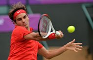 Switzerland's Roger Federer returns the ball against Uzbekistan's Denis Istomin during their men's singles third round tennis match during the 2012 London Olympic Games at the All England Tennis Club in Wimbledon, southwest London. Federer moved into the Olympic Games quarter-finals with a 7-5, 6-3 win over Istomin